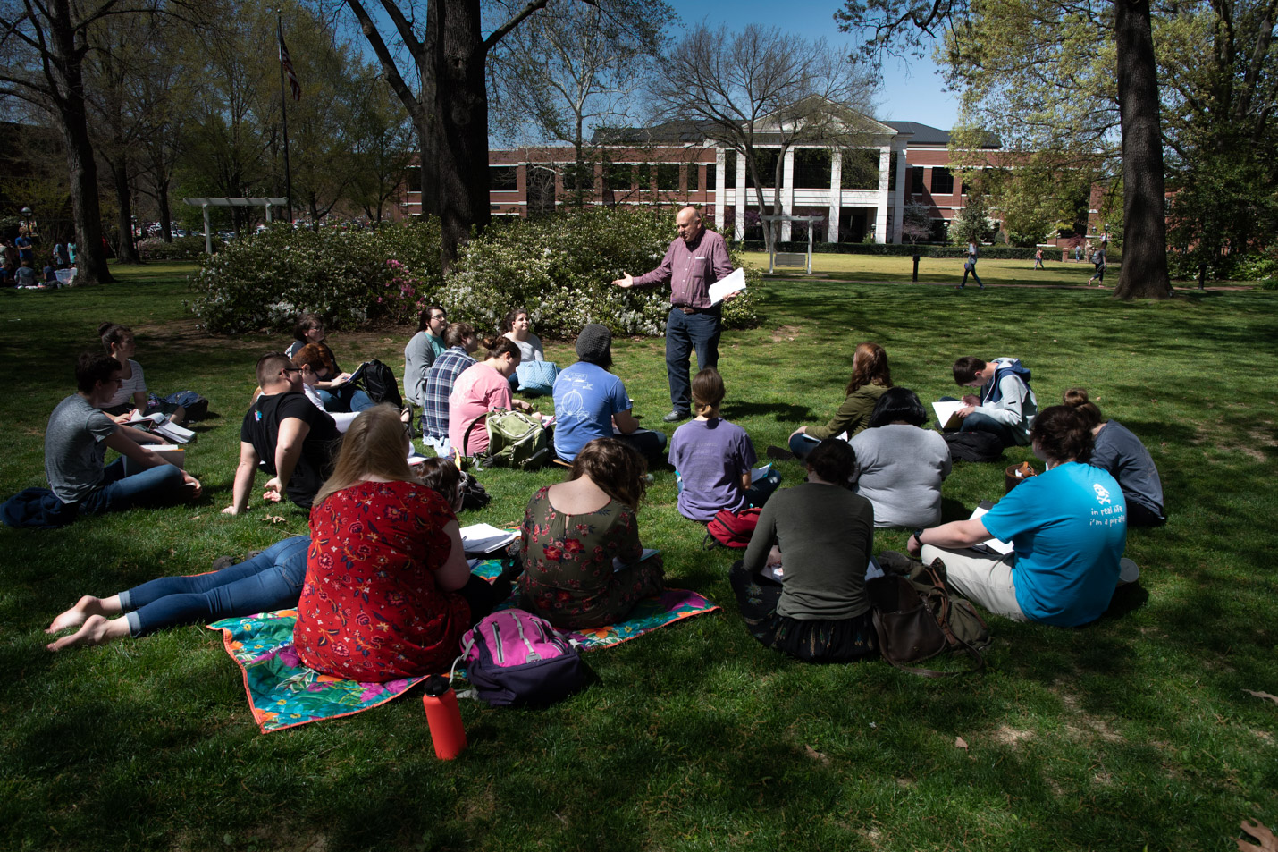 This is a photo of Dr. Ross Cochran and his class outside on the Front Lawn.