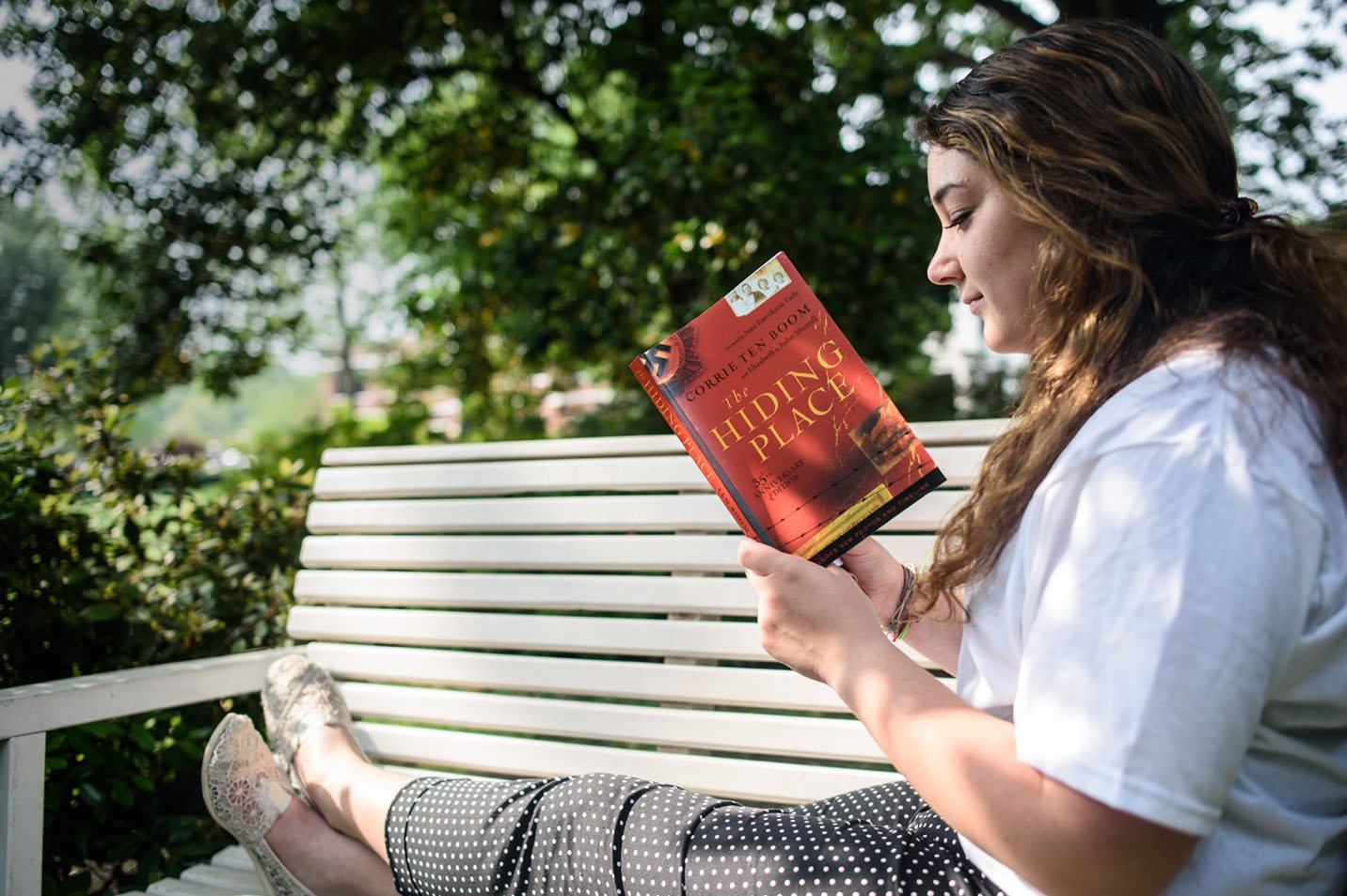 A photo of a student reading The Hiding Place by Corrie Ten Boom.