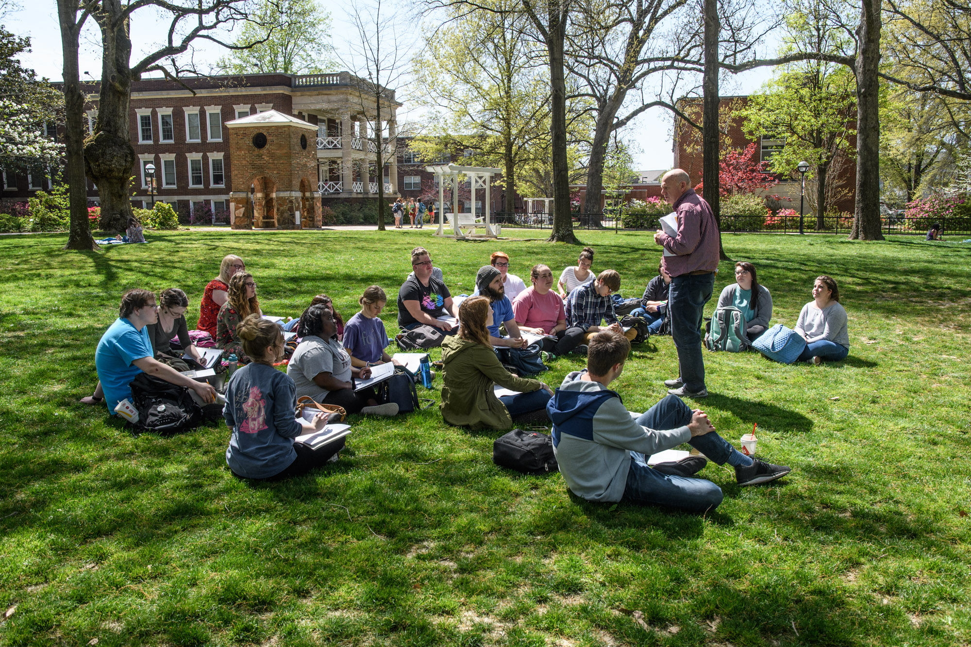 This is a photo of students having class outside on the front lawn.